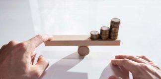 Dźwignia finansowa symbolizowana przez monety na równoważni